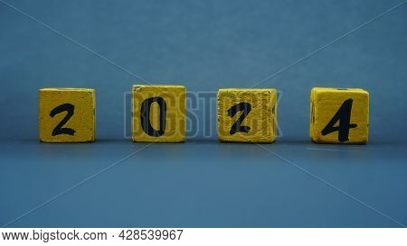 Wooden Block Calendar With Numbers For 2024. Yellow On A Dark Background