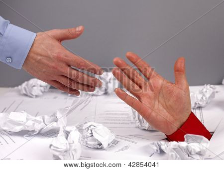 Businessman drowning in paperwork reaching for assistance and support