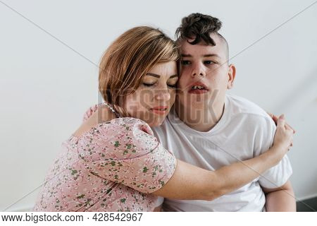 Mother Hugging Disabled Boy 17 Years Old In Wheelchair With Cerebral Palsy Over White Background. Wo