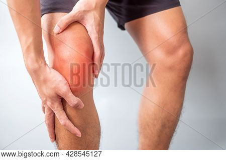 Man With Muscle Pain On Grey Background. Elderly Have Knee Ache Due To Runners Knee Or Patellofemora