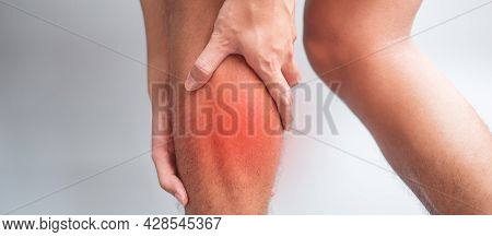 Adult Male With His Muscle Pain On Gray Background. Elderly Man Having Leg Ache Due To Calf Muscle P