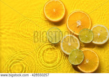 Citrus Fruits In Yellow Water Background With Concentric Circles And Ripples. Refreshing Summer Conc