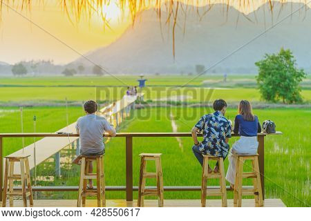 Back View Of People Sit For Resting And Waiting For Time To Take Photos Of The Sunset On The Farmer'