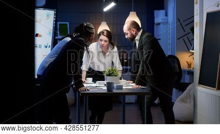 In Corporate Office Meeting Room Diverse Group Of Businesspeople Lean On Conference Table Brainstorm