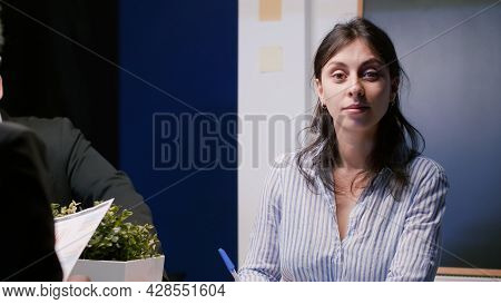 Portrait Of Smiling Businesswoman Looking Into Camera While Sitting At Conference Table In Company M