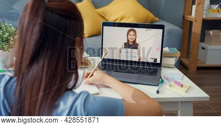 Young Asia Girl With Casual Use Computer Laptop Video Call Learn Online With Teacher Write Lecture N