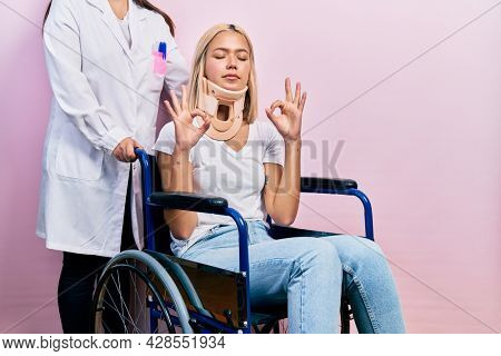 Beautiful blonde woman sitting on wheelchair with collar neck relax and smiling with eyes closed doing meditation gesture with fingers. yoga concept.
