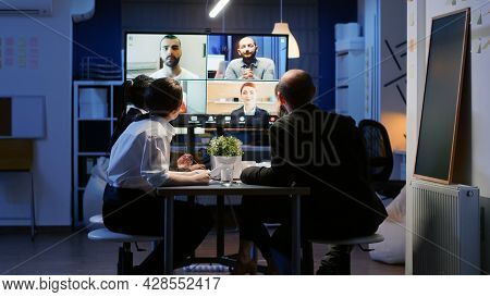 Diverse Group Of Business Teamwork Discussing With Remote Coworkers During Online Videocall Conferen