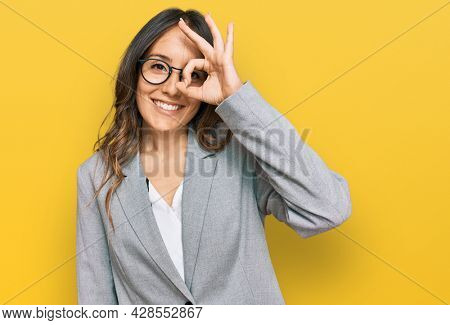 Young brunette woman wearing business clothes doing ok gesture with hand smiling, eye looking through fingers with happy face.