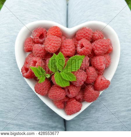 A Woman Farmer Holds A Heart-shaped Plate On Her Lap, In Which There Is A Ripe Raspberry With A Leaf