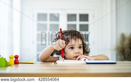 Cute Little Girl Sit At Desk At Home Doing Homework, Reading, Writing And Painting. Children Paint.