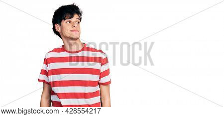 Handsome hipster young man wearing casual striped t shirt smiling looking to the side and staring away thinking.