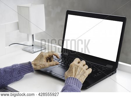 Elderly Woman Wrinkled Hands Typing On The Laptop With Empty White Screen For Copy Space.