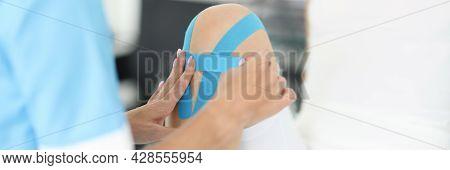 Rehabilitation Therapist Gluing Blue Tapes On Woman Knee Closeup