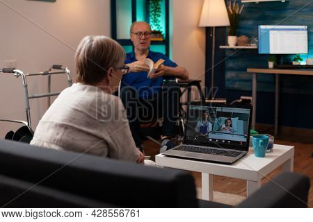 Old Grandmother Calling Doctor In Hospital Ward Clinic To Check Healthcare Diagnosis On Video Call C