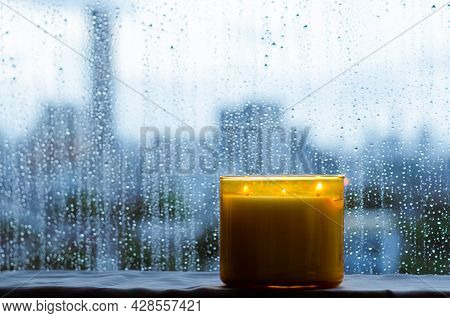 Burning Aroma Candle Puts Near By Window That Have Rain Drop In Monsoon Season. Zen And Relax Concep