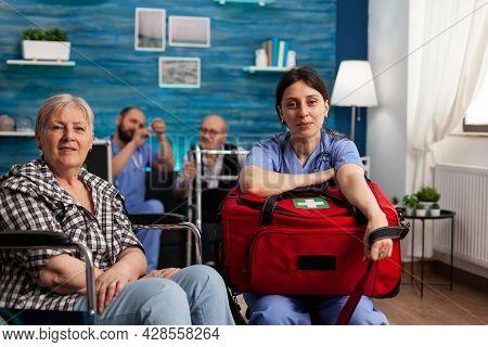Portrait Of Support Nurse Worker Holding Medicine Kit Bag Sitting Beside Disabled Senior Patient Loo