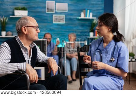 Support Assistant Worker Explaining Healthcare Treatment To Disabled Senior Man In Wheelchair During
