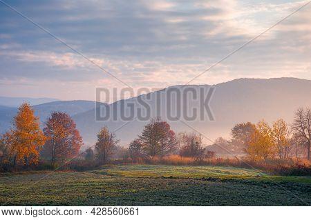 Foggy Rural Landscape At Sunrise. Beautiful Mountainous Countryside In Late Autumn Season. Empty Fie
