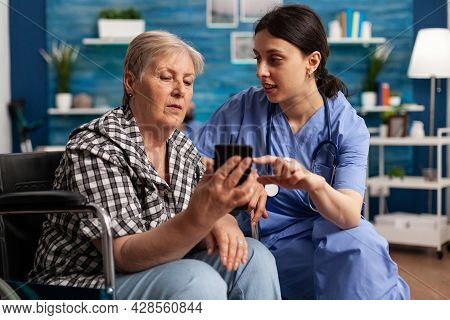 Nurse Helping Retired Senior Woman In Wheelchair To Use Smartphone During Social Service. Elderly Pe