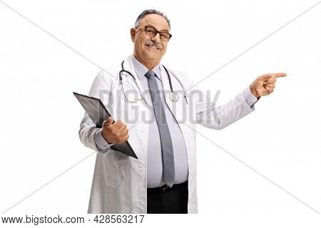Smiling mature doctor standing with a clipboard and pointing isolated on white background