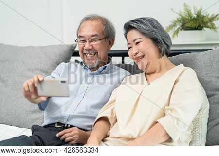 Asian Senior Elderly Couple Use Phone Remote Video Call With Family. Happy Older Grandparent Holding
