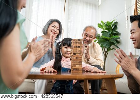 Asian Happy Family Enjoy Play Toy Block With Little Daughter In House. Grandparents And Young Loving