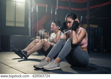 Active Sportsman And Woman Sit-up On Floor For Abs Workout In Stadium. Group Of Multiethnic Fitness