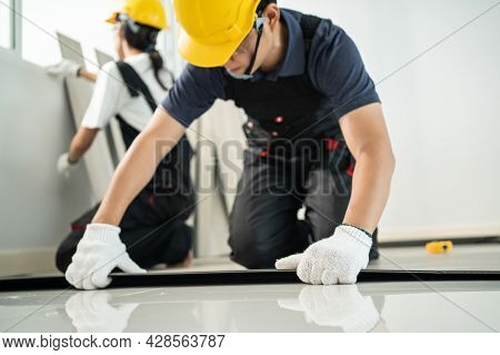 Asian Craftsman Worker People Installs Laminate Board On Floor At Home. Attractive Joiner And Carpen