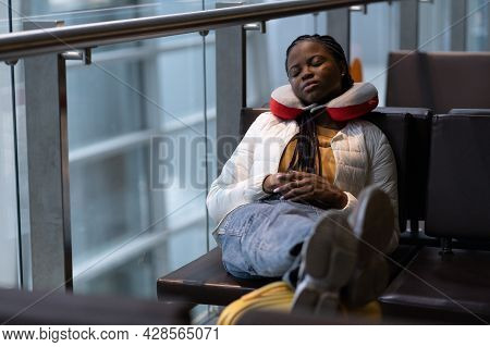 Tired Woman Sleep In Airport On Chair With Legs On Suitcase Waiting For Transit Flight Departure. Bl