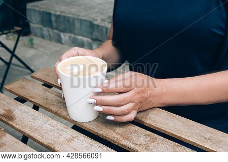Female Hands And A White Ceramic Cup Of Cappuccino With Latte Art On A Wooden Table. Open-air Rustic