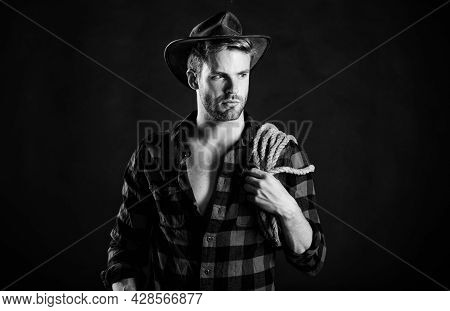 Lassoing On Prairie. Man Unshaven Cowboy Black Background. Cowboy Wearing Hat Hold Rope. Lasso Tool