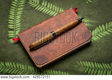 small leather-bound journal with a stylish pen against green paper with leaf inclusions, journaling concept