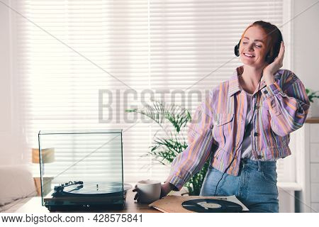Young Woman Drinking Coffee While Listening To Music With Turntable At Home