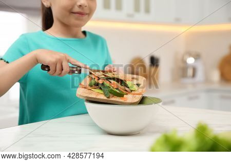 Little Girl With Cutting Board And Knife Scraping  Vegetable Peels Into Bowl On Kitchen Table, Close