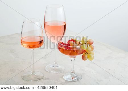 Rose Wine And Summer Drinks Champagne Cocktail With Grapes At Wine Tasting. Group Glasses Of Pink Wi