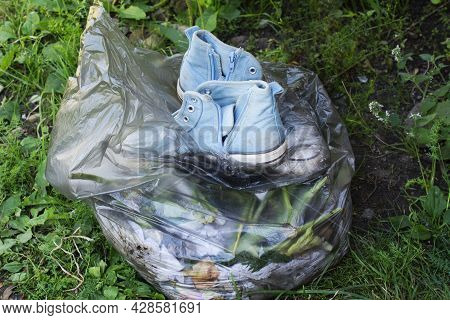 Pair Old Dirty Blue Sneakers In Black Garbage Bag On Green Grass Background