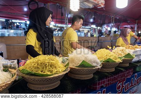 Thai Food On The Street In Phuket. Yellow And White Noodles At The Market, Where Cooks Can Cook Them