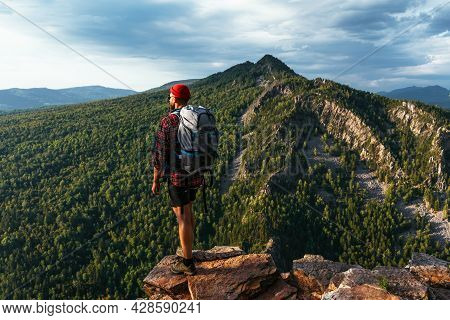 A Traveler With A Backpack In The Mountains At Sunset. Hiking In The Mountains. Travel To Bashkiria,