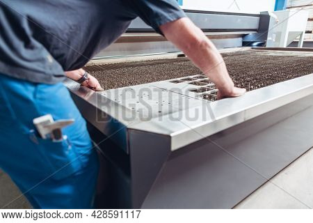 Worker placing work piece on table of jet cutting machine