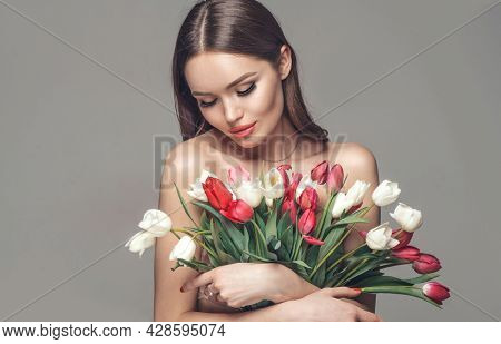 Beauty glamour girl with Spring tulips Flower bouquet. Beautiful young woman with a Bunch of colorful Tulip flowers. Happy model posing with summer flowers. Valentine's Day. Birthday party. Gift.