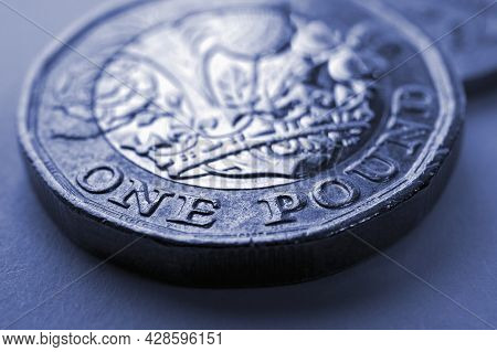 1 One British Pound Coin Close-up. Blue Tinted Background About Economy, Business, Finance Or Bankin