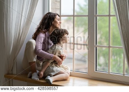 Curious Mom And Kid Boy Looking Outside Sitting On Window Sill. Caring Mother Or Babysitter Explorin