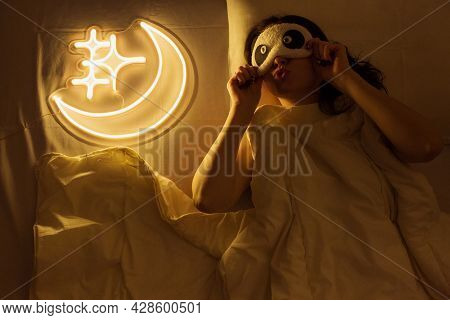 Beautiful Girl With Neon Signs. A Beautiful Girl Is Sleeping Next To A Neon Sign With The Moon And S