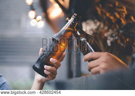 Cropped Image Of Friends Having Fun Clinking Bottles Of Beer While Resting At The Pub