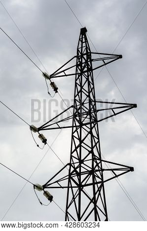 A Metal High-voltage Pole Against A Gray Overcast Sky. The Pylon Of A High-voltage Line. Transportat