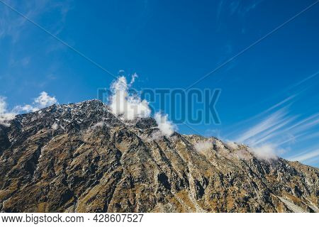 Scenic Autumn Sunny Landscape With High Rocky Mountain With Peaked Top In Low Clouds Under Blue Sky.