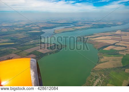 Land View Through The Airplane Window. Fields, Roads, Rivers From A Bird's Eye View. Porthole. Look