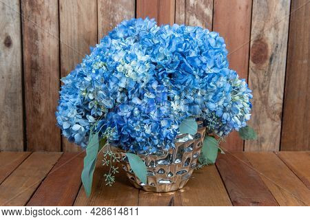Beautiful Bouquet Of Arranged Blue Hydrongea Flowers In A Silver Vase Given As An Emotional Sentimen