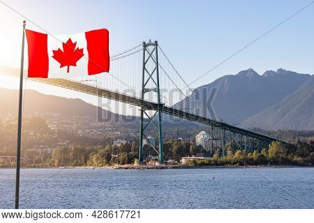 View Of The Famous Lions Gate Bridge From Stanley Park In A Modern City. Downtown Vancouver, British